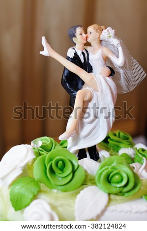 bride and groom figurines on a cake - stock photo