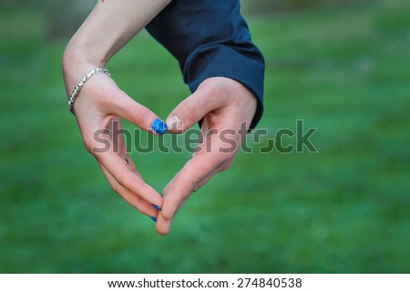 Bride and groom hands making heart.