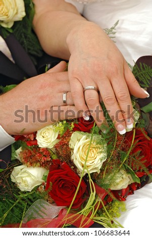 Bride and groom hands with rose petals