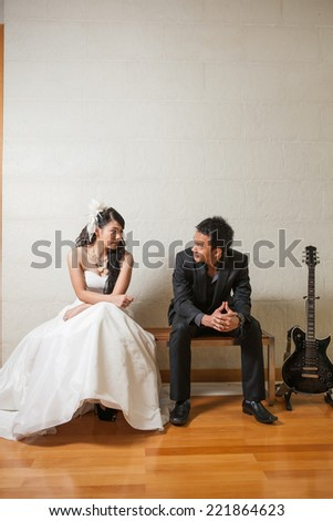Bride and groom happy sitting on the wooden bench with back guitar on white background.