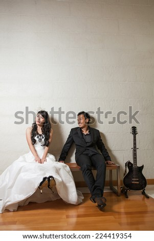 Bride and groom happy sitting on the wooden bench with back guitar on white background. - stock photo