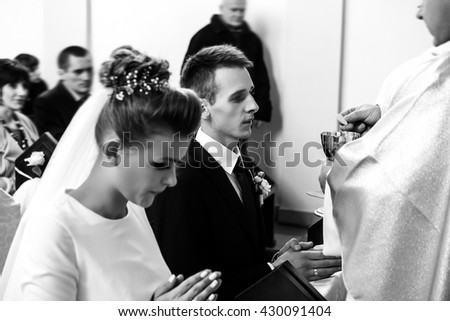 bride and groom having communion with priest on knees at wedding ceremony in church - stock photo
