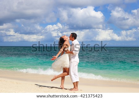 Bride and groom having fun at sandy beach, Tropical wedding concept