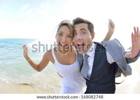 Bride and groom having fun at the beach