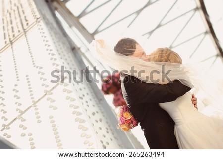 Bride and groom having fun on a bridge - stock photo