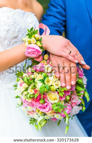 Bride and groom hold bouquet of flowers in hands with rings.