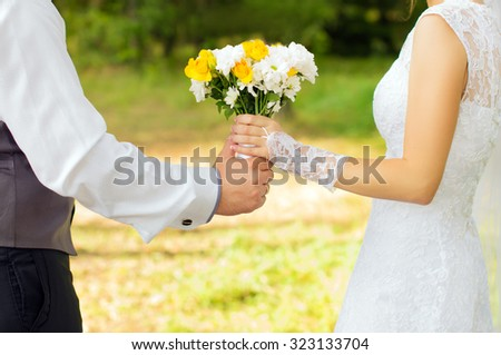 Bride and groom holding a bouquet of flowers - stock photo