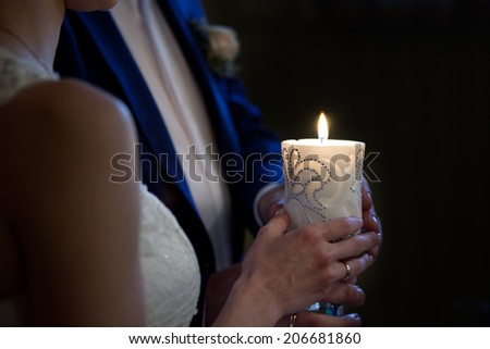 bride and groom holding a candle in church - stock photo