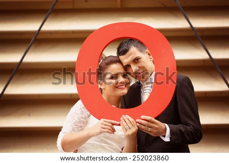 Bride and groom holding a O letter  - stock photo