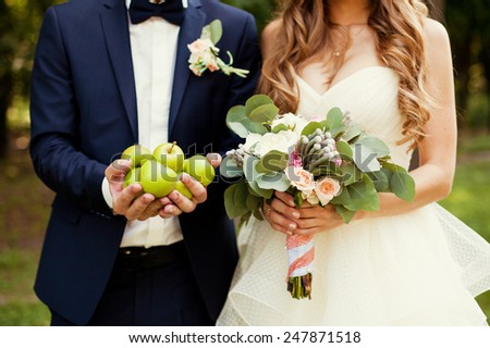 bride and groom holding bouquet and apples - stock photo