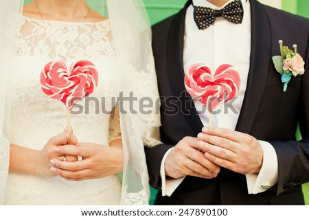 bride and groom holding candies - stock photo