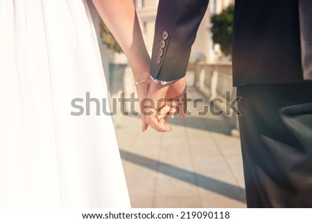 bride and groom holding each other's hands - stock photo