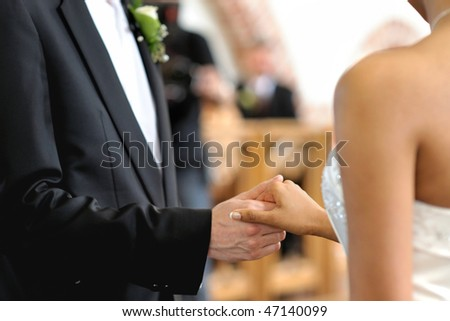 Bride and groom holding each other's hands during wedding ceremony