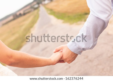 Bride and groom holding hand each other - stock photo