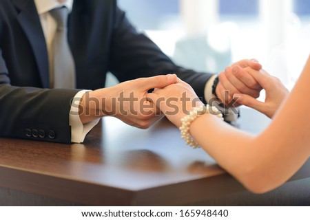 bride and groom holding hands at table