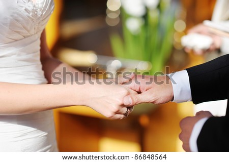 Bride and groom holding hands at the wedding ceremony
