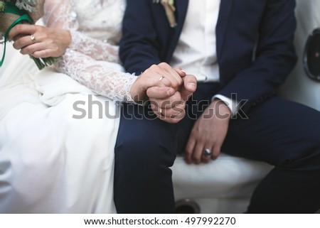 bride and groom holding hands close view