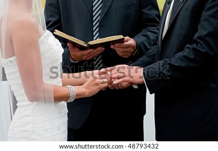 bride and groom holding hands during ring exchange part of an outdoor wedding ceremony - stock photo