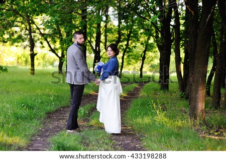 bride and groom holding hands in a stylish outfit on a background of the forest road.