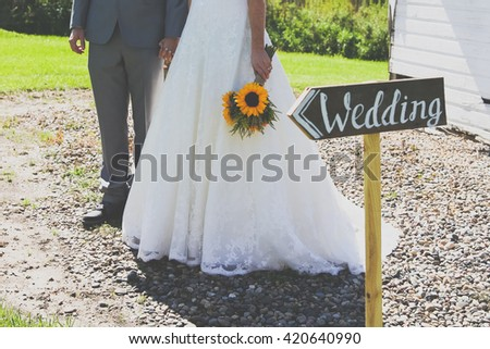 Bride and groom holding hands in front of wedding sign vintage toned. - stock photo