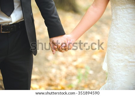 bride and groom holding hands in park