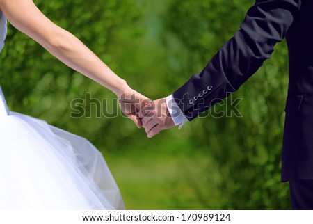 Bride and groom holding hands in summer day - stock photo