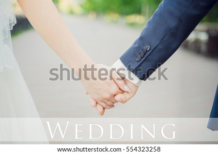 Bride and groom holding hands in the park