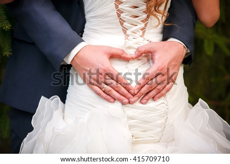 bride and groom holding hands in the shape of heart - stock photo