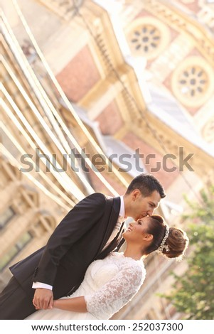 Bride and groom holding hands near church - stock photo