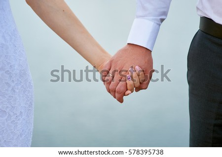bride and groom holding hands on a background of water