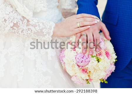 Bride and groom holding hands on a bouquet. Wedding rings. Wedding vows. - stock photo