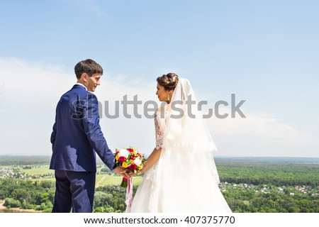 Bride and groom holding hands outdoors.