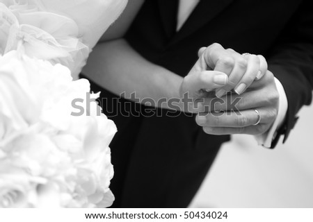 Bride and groom holding hands with her bouquet - stock photo