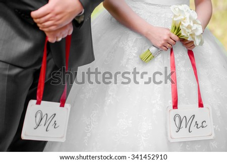 bride and groom holding Mr&Mrs labels in their arms - stock photo