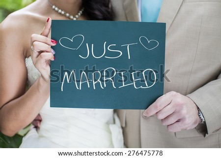 Bride and Groom holding small blackboard with message Just Married - stock photo