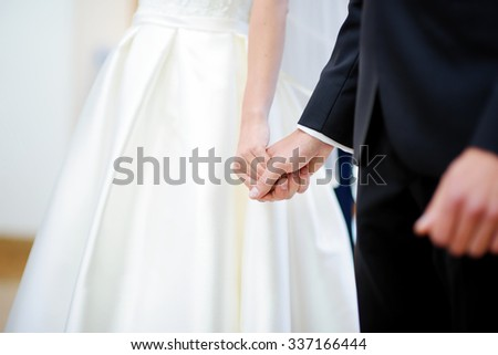 Bride and groom holding their hands during wedding ceremony - stock photo