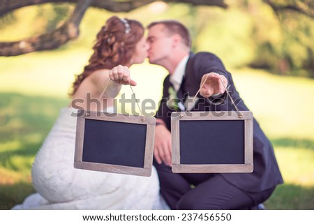 bride and groom holding two empty wooden signs while kissing - stock photo