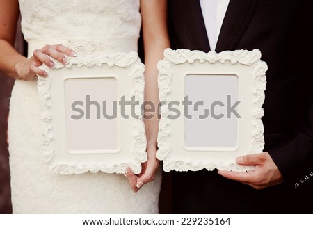 Bride and groom holding vintage photo frames, cut out - stock photo