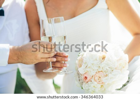 Bride and groom holding wedding bouquet and glass of champagne
