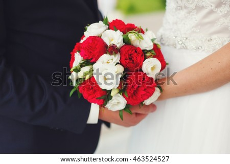 Bride and groom holding wedding bouquet of red and white roses. Marriage concept
