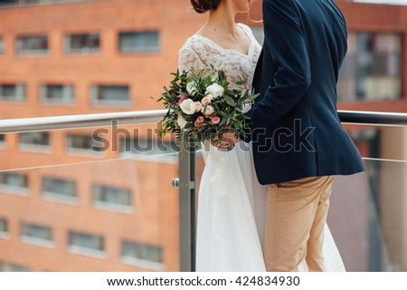 Bride and groom holding wedding bouquet together . Hug . beautiful hair. bride in a beautiful lace dress , the groom with a wooden butterfly - stock photo
