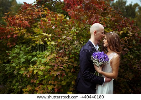 Bride and groom hug standing in a big red bush