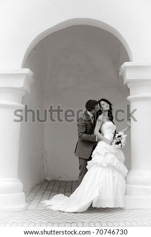bride and groom hugging gently into the arch