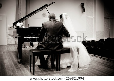 bride and groom in a concert hall near the piano