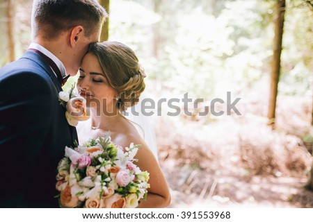 Bride and groom in a park kissing.couple newlyweds bride and groom at a wedding in nature green forest are kissing photo portrait.Wedding Couple - stock photo
