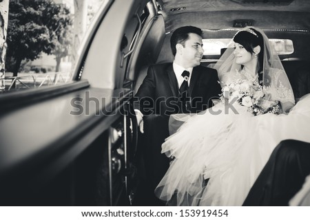 bride and groom in a wedding limousine with a bouquet - stock photo