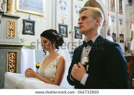 Bride and groom in the church during the Christian wedding ceremony. - stock photo