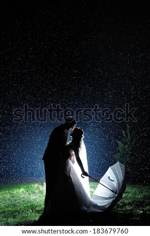 Bride and groom in the night rain. Dramatic moment.  - stock photo