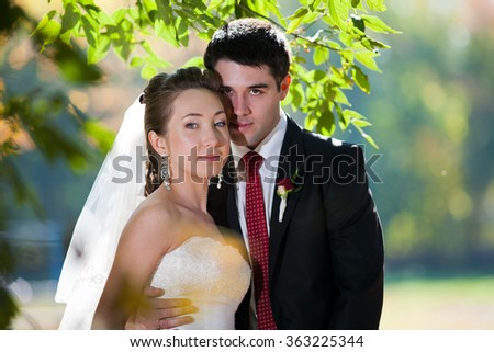 bride and groom in their wedding day near autumn tree