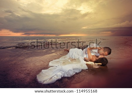 Bride and groom in their wedding outfits lying in the water on the beach and kissing. - stock photo